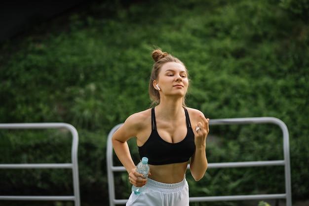 Młoda szczupła szczęśliwa kobieta działa w parku miejskim z butelką wody w rękach, sport, wesołość, sport miejski zdrowy styl życia, fitness, biegacz
