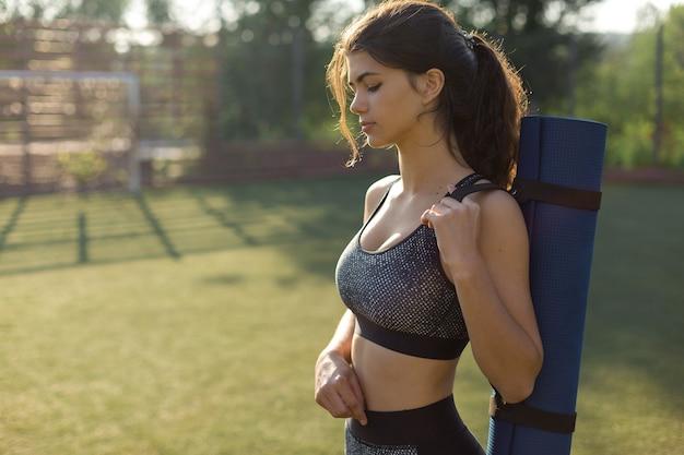 Młoda, szczupła, wysportowana dziewczyna w stroju sportowym z nadrukami z wężowej skóry wykonuje zestaw ćwiczeń. fitness i zdrowy styl życia.