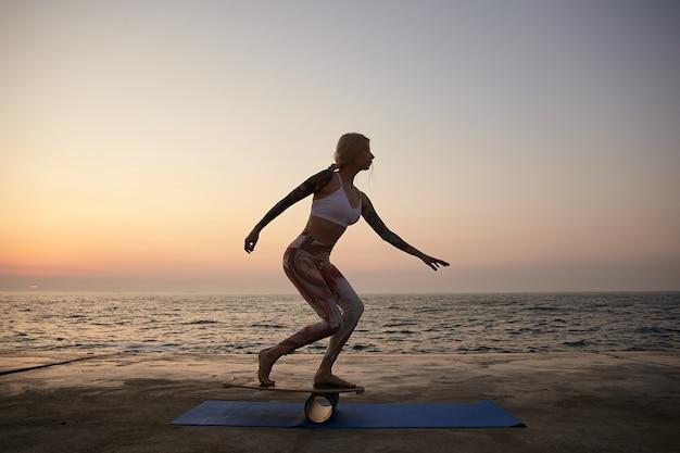 Młoda szczupła wytatuowana kobieta o dobrej kondycji fizycznej balansująca na pokładzie nad morzem, wcześnie rano wykonująca ćwiczenia z balanserem na wybrzeżu, ubrana w sportowy top i legginsy
