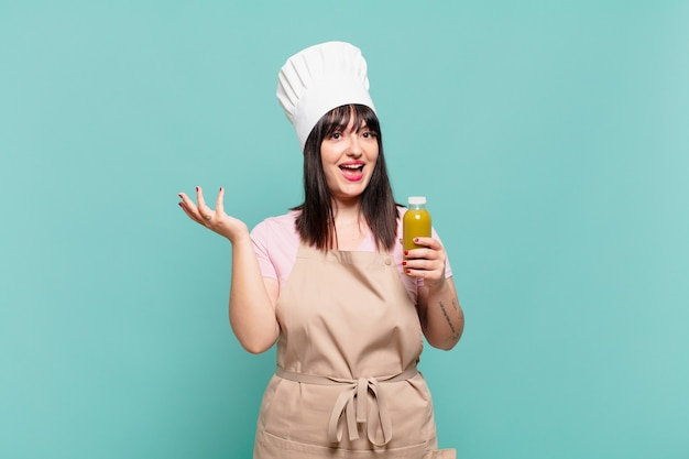 Młoda szefowa kuchni czuje się szczęśliwa, zaskoczona i wesoła, uśmiechnięta z pozytywnym nastawieniem, realizująca rozwiązanie lub pomysł