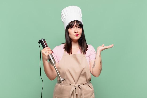 Młoda szefowa kuchni czuje się zakłopotana i zdezorientowana, wątpi, waży lub wybiera różne opcje ze śmiesznym wyrazem twarzy