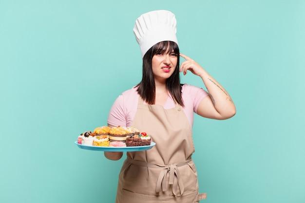 Młoda szefowa kuchni czuje się zdezorientowana i zakłopotana, pokazując, że jesteś szalony, szalony lub oszalały