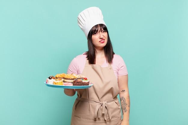 Młoda szefowa kuchni czuje się zdziwiona i zdezorientowana, z tępym, oszołomionym wyrazem twarzy, patrzącą na coś nieoczekiwanego