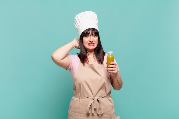 Młoda szefowa kuchni czuje się zestresowana, zmartwiona, niespokojna lub przestraszona, z rękami na głowie, panikując z powodu błędu