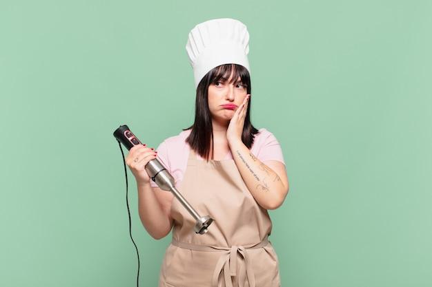 Młoda szefowa kuchni czuje się znudzona, sfrustrowana i senna po męczącym, nudnym i żmudnym zadaniu, trzymając twarz dłonią