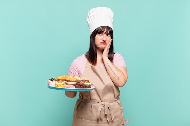 Młoda szefowa kuchni czuje się znudzona, sfrustrowana i senna po męczącym, nudnym i żmudnym zadaniu, trzymając twarz ręką