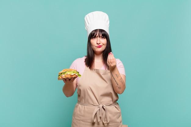 Młoda szefowa kuchni robi gest kaprysu lub pieniędzy, mówiąc, że masz spłacić swoje długi!