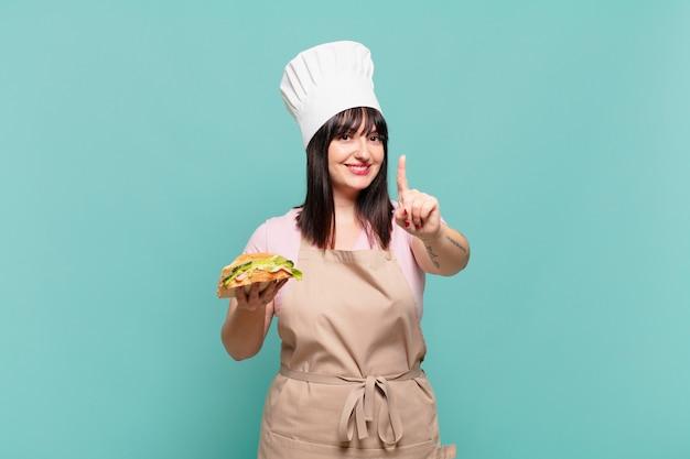 Młoda szefowa kuchni uśmiecha się dumnie i pewnie, triumfalnie wykonując pozę numer jeden, czując się jak lider