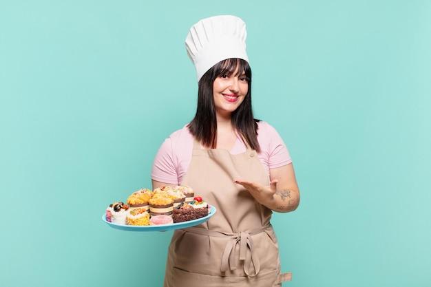 Młoda szefowa kuchni uśmiecha się radośnie, czuje się szczęśliwa i pokazuje koncepcję w przestrzeni kopii z dłonią
