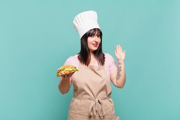 Młoda szefowa kuchni uśmiecha się radośnie i radośnie, machając ręką, witając cię i pozdrawiając lub żegnając się