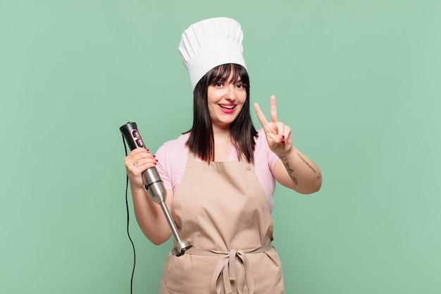 Młoda szefowa kuchni uśmiechnięta i wyglądająca na szczęśliwą, beztroską i pozytywną, gestem zwycięstwa lub pokoju jedną ręką