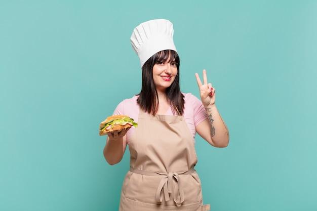 Młoda szefowa kuchni uśmiechnięta i wyglądająca przyjaźnie, pokazująca numer dwa lub drugi z ręką do przodu, odliczając w dół