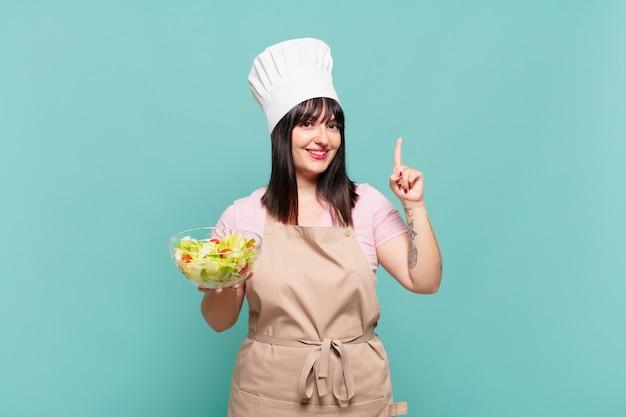 Młoda szefowa kuchni uśmiechnięta i wyglądająca przyjaźnie, pokazująca numer jeden lub pierwsza z ręką do przodu, odliczająca