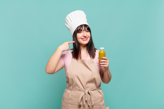 Młoda szefowa kuchni uśmiechnięta pewnie, wskazując na swój szeroki uśmiech, pozytywna, zrelaksowana, zadowolona postawa