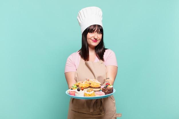 Młoda szefowa kuchni uśmiechnięta radośnie z przyjaznym, pewnym siebie, pozytywnym spojrzeniem, oferująca i pokazująca przedmiot lub koncepcję