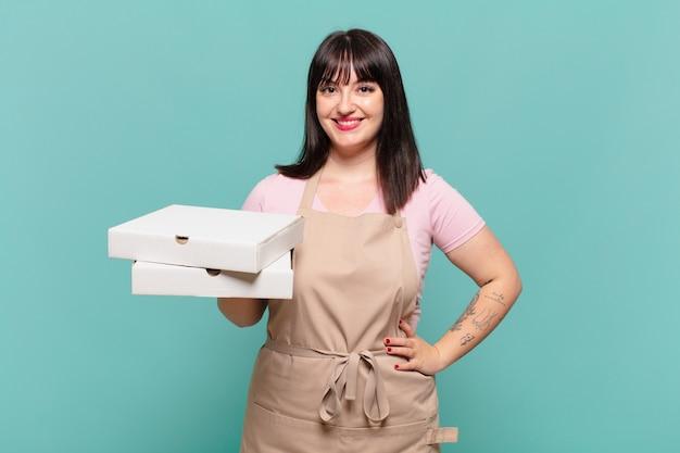 Młoda szefowa kuchni uśmiechnięta radośnie z ręką na biodrze i pewna siebie, pozytywna, dumna i przyjazna postawa