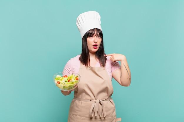 Młoda szefowa kuchni wygląda na zszokowaną i zaskoczoną z szeroko otwartymi ustami, wskazując na siebie
