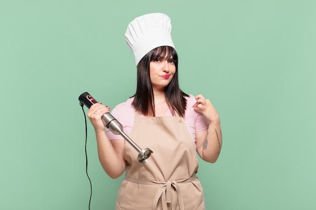 Młoda szefowa kuchni wyglądająca na arogancką, odnoszącą sukcesy, pozytywną i dumną, wskazującą na siebie