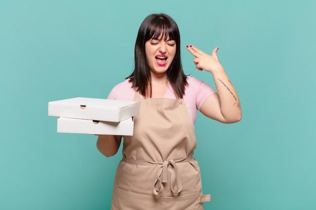 Młoda szefowa kuchni wyglądająca na niezadowoloną i zestresowaną, gest samobójczy, wykonujący znak pistoletu ręką, wskazujący na głowę