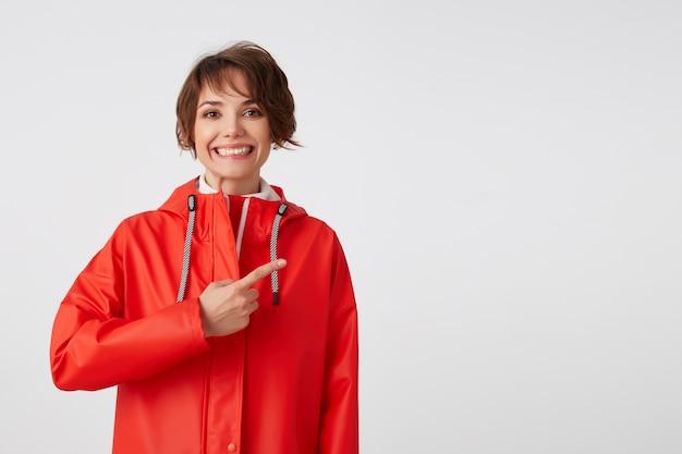 Młoda, szeroko uśmiechnięta śliczna, krótkowłosa dama ubrana w biały golf i czerwony płaszcz przeciwdeszczowy, chce zwrócić twoją uwagę na miejsce na kopię, wskazuje palcem w prawo. na stojąco.
