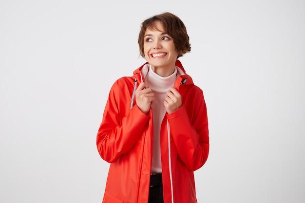 Młoda, szeroko uśmiechnięta śliczna, krótkowłosa dama ubrana w biały golf i czerwony płaszcz przeciwdeszczowy, odwracająca wzrok ze szczęśliwym wyrazem twarzy, stojąca.