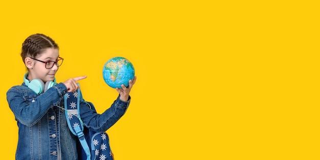 Młoda szkoła teen dziewczyna dziecko 8-9 lat z plecakiem trzymać w ręku globus świata samodzielnie na żółtym tle portret studyjny dzieci edukacja podróży za granicę koncepcji stylu życia. długi, szeroki baner