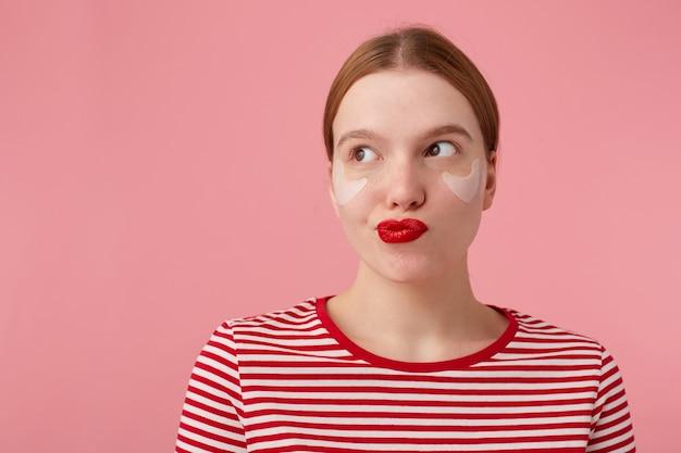 Młoda tajemnicza rudowłosa dama z czerwonymi ustami i łatami pod oczami, ubrana w czerwoną koszulkę w paski, zdezorientowana spojrzenia na lewą stronę, coś knuje, stoi na różowym tle.