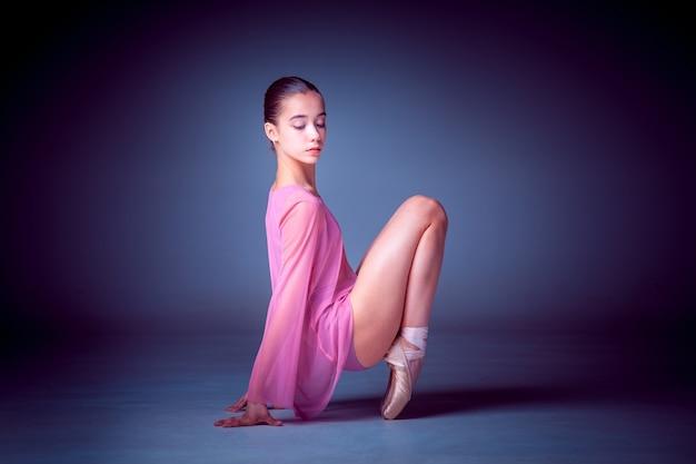 Młoda tancerka baleriny pokazująca swoje techniki na liliowym tle