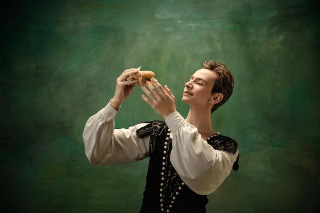 Młoda tancerka baletowa jako postać królewny śnieżki z burgerem w lesie.