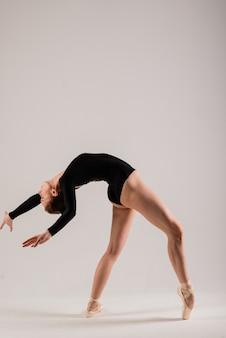 Młoda tancerka baletowa na białej ścianie