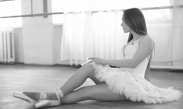 Młoda tancerka baletowa na rozgrzewce. balerina przygotowuje się do występu w studiu. dziewczyna w baletowych ubraniach i butach ugniata przy poręczach.
