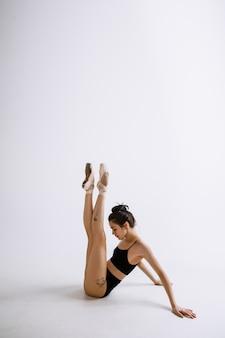 Młoda tancerka baletowa w czarnym body na białej ścianie studia