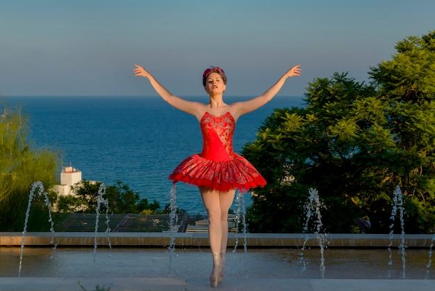 Młoda tancerka baletowa z czerwonym stroju taniec na zewnątrz