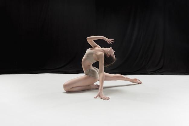 Młoda tancerka nastolatków na białej podłodze.