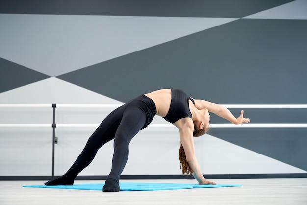 Młoda tancerka rozciągająca się na podłodze