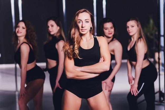 Młoda tancerka striptizu poruszająca się na wysokich obcasach na scenie tańca na rurze.