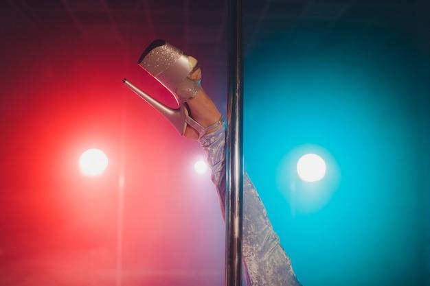 Młoda tancerka striptizu poruszająca się na wysokich obcasach na scenie w nocnym klubie ze striptizem, taniec na rurze.
