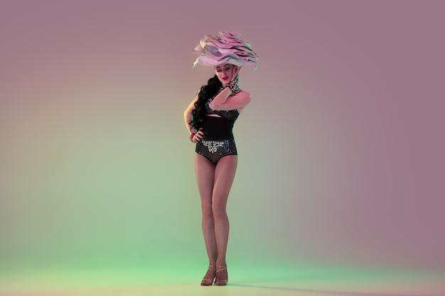 Młoda tancerka z ogromnymi kwiatowymi kapeluszami w neonowym świetle na ścianie gradientowej