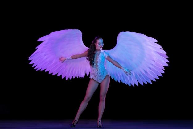 Młoda tancerka ze skrzydłami anioła w świetle neonu na czarnej ścianie