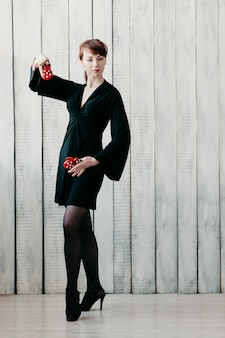 Młoda tańcząca dziewczyna w czarnej sukni z czerwonymi kastanietami