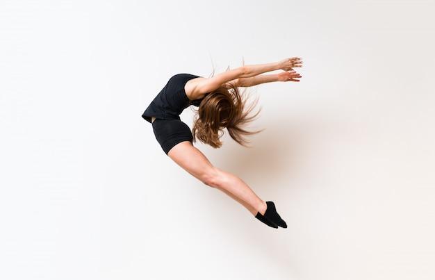 Młoda taniec dziewczyna nad odosobnioną biel ścianą