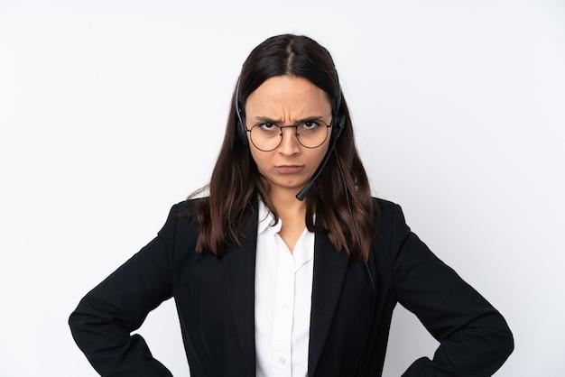 Młoda telemarketer kobieta na biel ścianie gniewnej