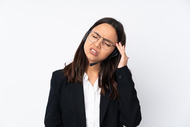 Młoda telemarketer kobieta na biel ścianie z migreną