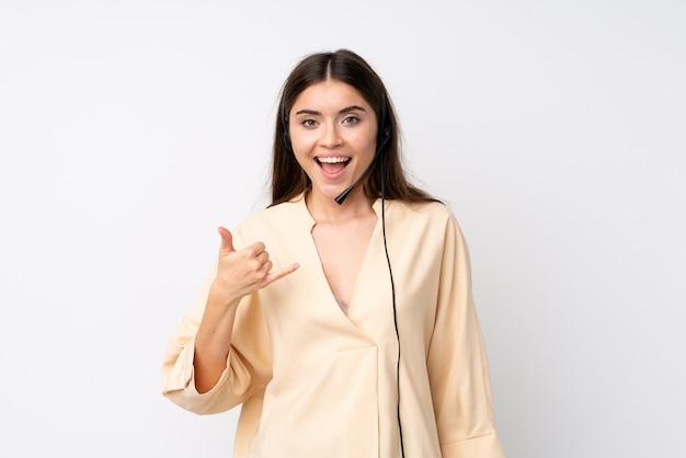 Młoda telemarketer kobieta nad odosobnioną biel ścianą robi telefonu gestowi