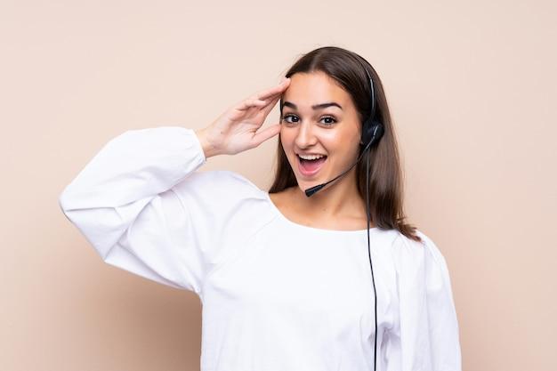 Młoda telemarketer kobieta nad odosobnionym tłem z niespodzianką i zszokowanym wyrazem twarzy