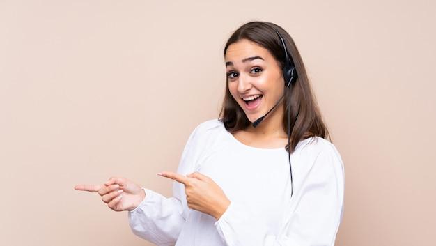 Młoda telemarketer kobieta nad odosobnionym tłem zaskakującym i wskazuje stronę