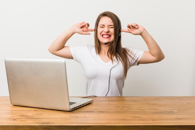 Młoda telemarketer kobieta obejmujące uszy rękami