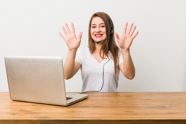 Młoda telemarketer kobieta pokazuje liczbę dziesięć z rękami.