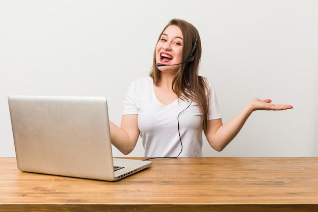 Młoda telemarketer kobieta pokazuje mile widziany wyrażenie.