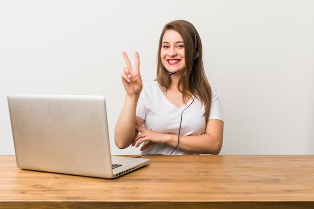 Młoda telemarketer kobieta pokazuje numer dwa z palcami.